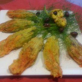 Fiori di zucca ripieni di miglio allo zafferano con capperi e olive.